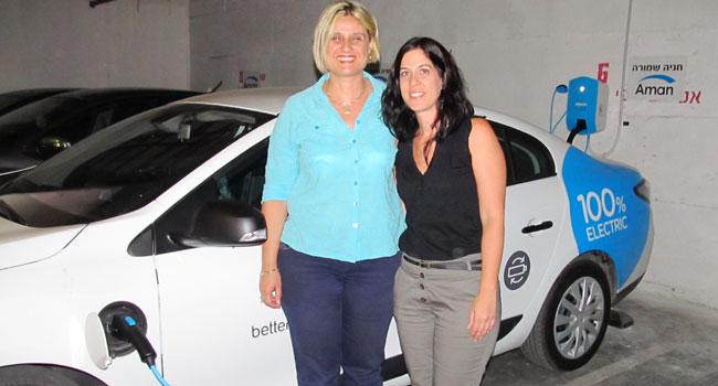 מיטל רוזמן - מנהלת תפעול משאבי אנוש בקבוצת אמן, ולימור סלמן - מנהלת רכש ורווחה בקבוצת אמן, על רקע המכונית החשמלית של בטר פלייס