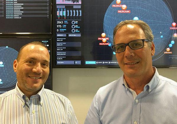 """מימין לשמאל על רקע ה-Global War Room: אמיר שמר, סמנכ""""ל מכירות וחבר הנהלה בניוטרון; ומוטי לנדס, דירקטור Global Customer Success"""