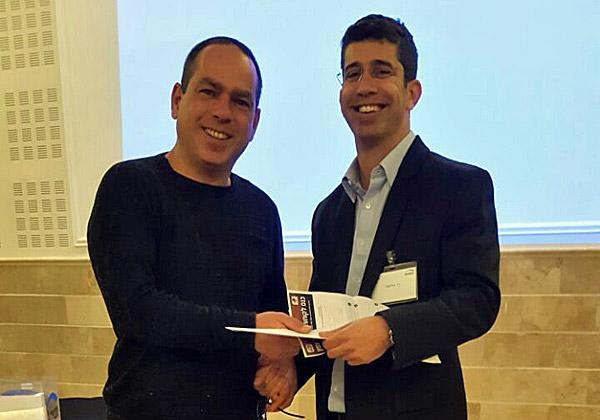 """ניר גולדווסר, מנהל חשב ERP, מעניק את הפרס למנהל התפעול של מפעל ש.צ.פ. צילום: יח""""צ"""